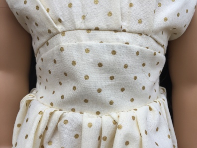 The waist of the gold/white dress